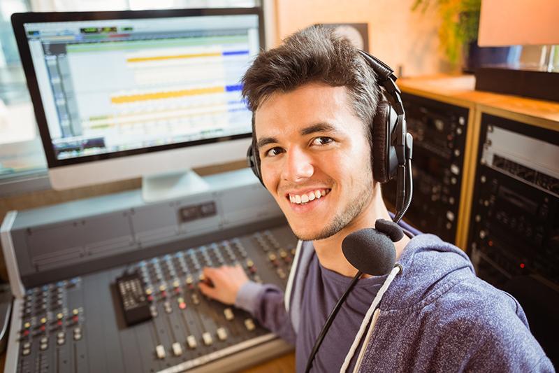 Student mixing audio in a studio